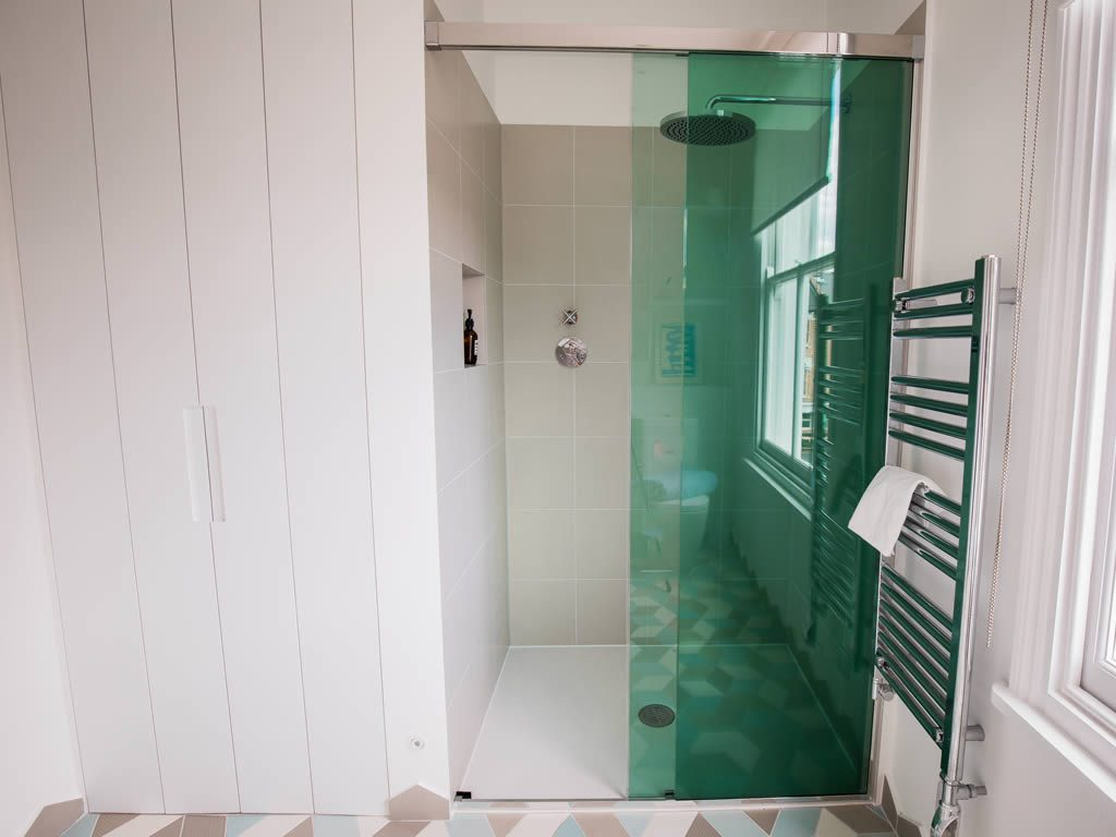Modern shower cabinet with green glass doors styled by Absolute Project Management