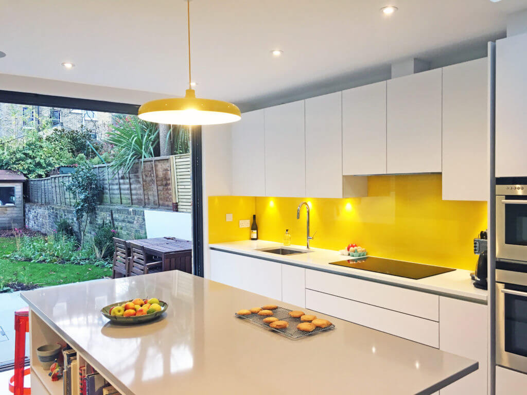 Kitchen with yellow splash-back lit with downlights, and an overhead pendant over the kitchen island