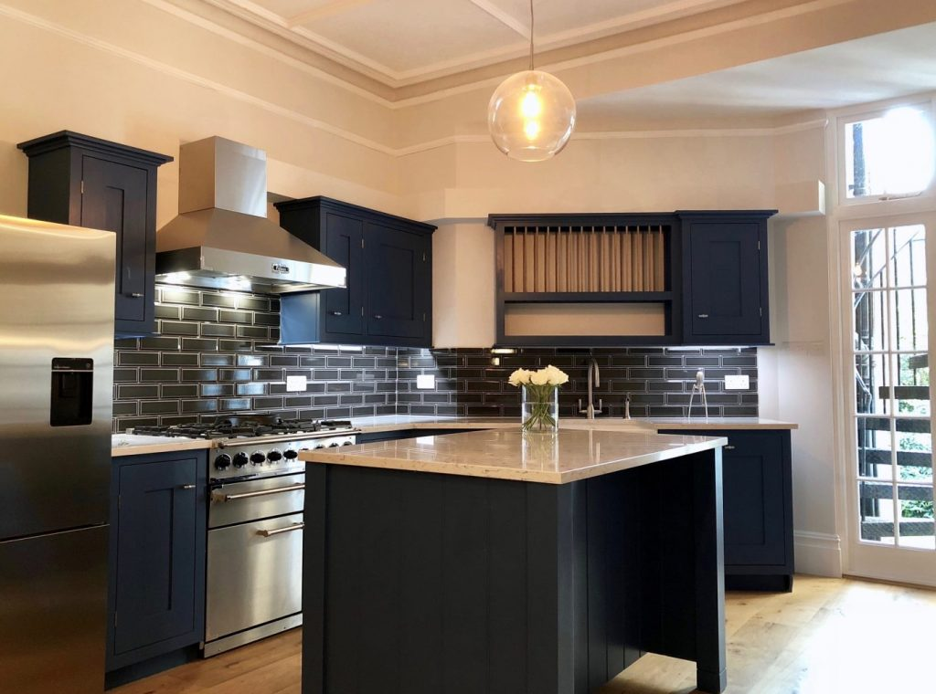 Navy kitchen with subway tiles, white worktop and brass ironmongery. `Renovation by Absolute Project Management.