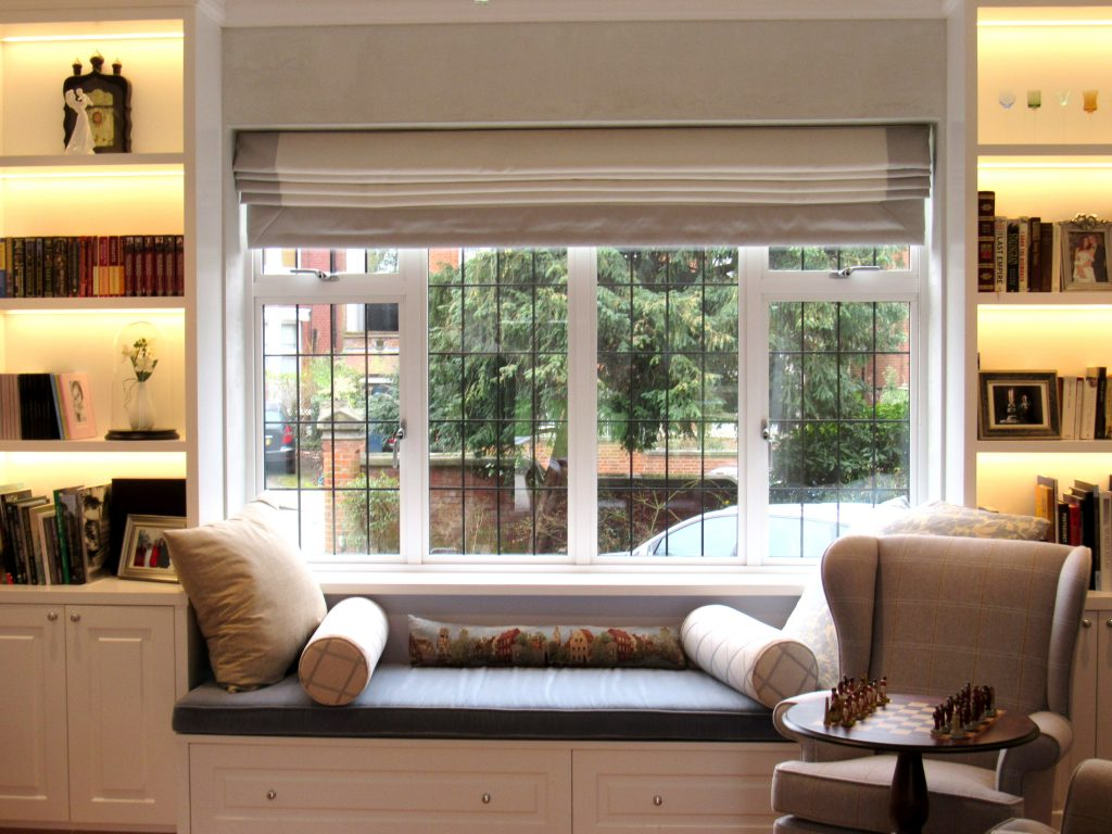 Shelves with concealed lighting either side of a window seat