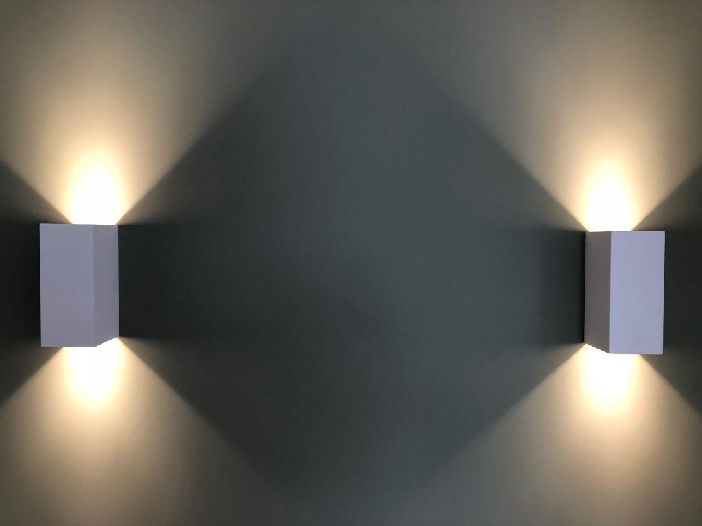 Wall lighting casting angular shadows on blue-grey wall
