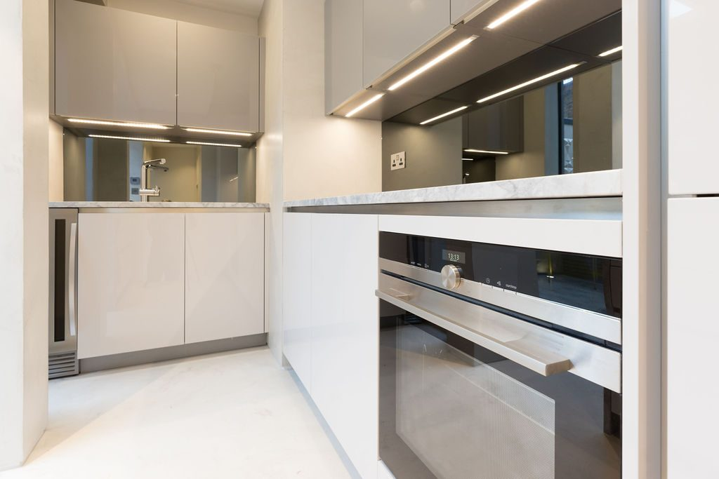 Modern white grey kitchen cabinetry, marble kitchen top and LED lights under the cupboards
