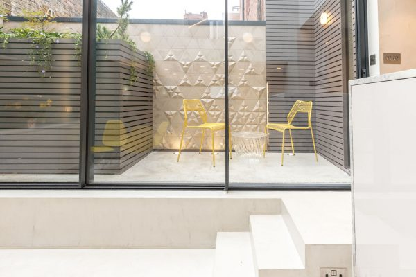 View of the outdoor space and the bright yellow chairs styled by Absolute Project Management