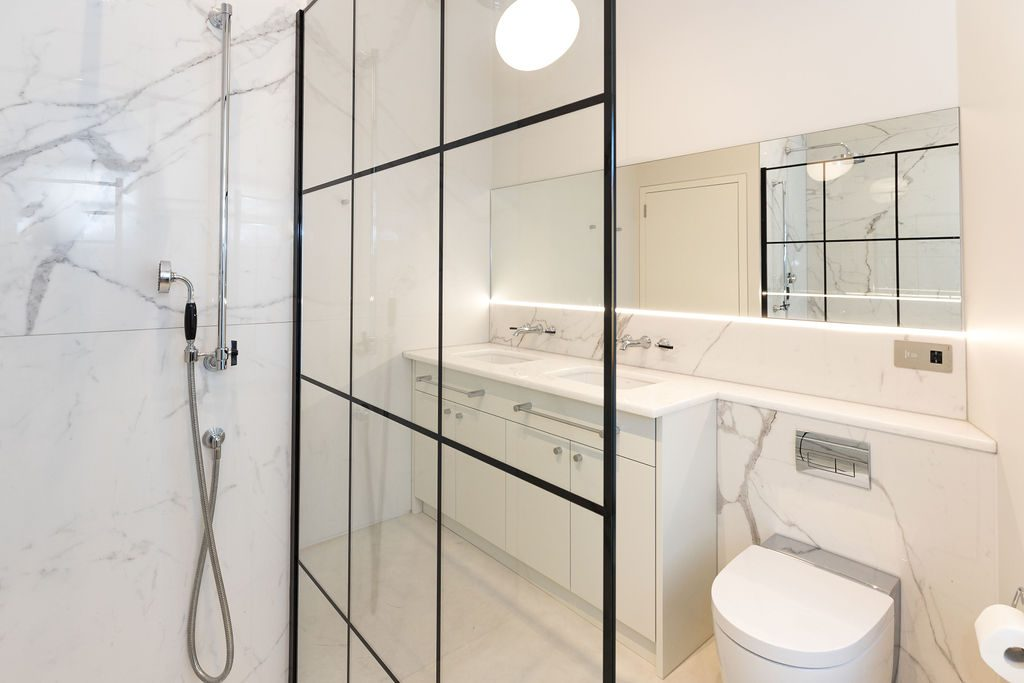 Modern bathroom with white marble wall tiles styled by Absolute Project Management