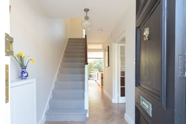 Grey carpet stairs and brown-white balustrades designed by Absolute Project Management