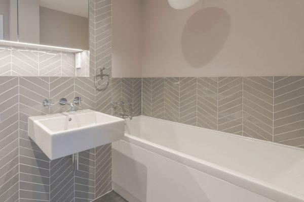 Modern bathroom, grey tiles, dusty pink walls styled by Absolute Project Management