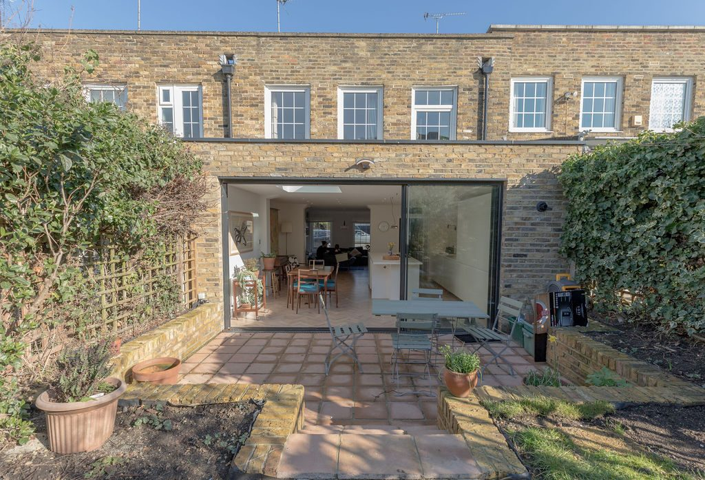 View of rear elevation of extended house in Old London Stock brick with fences grown over with plants.