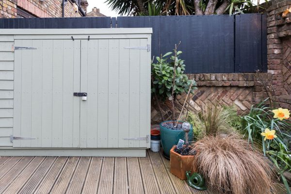 Cute pastel green storage space in the garden styled by Absolute Project Management