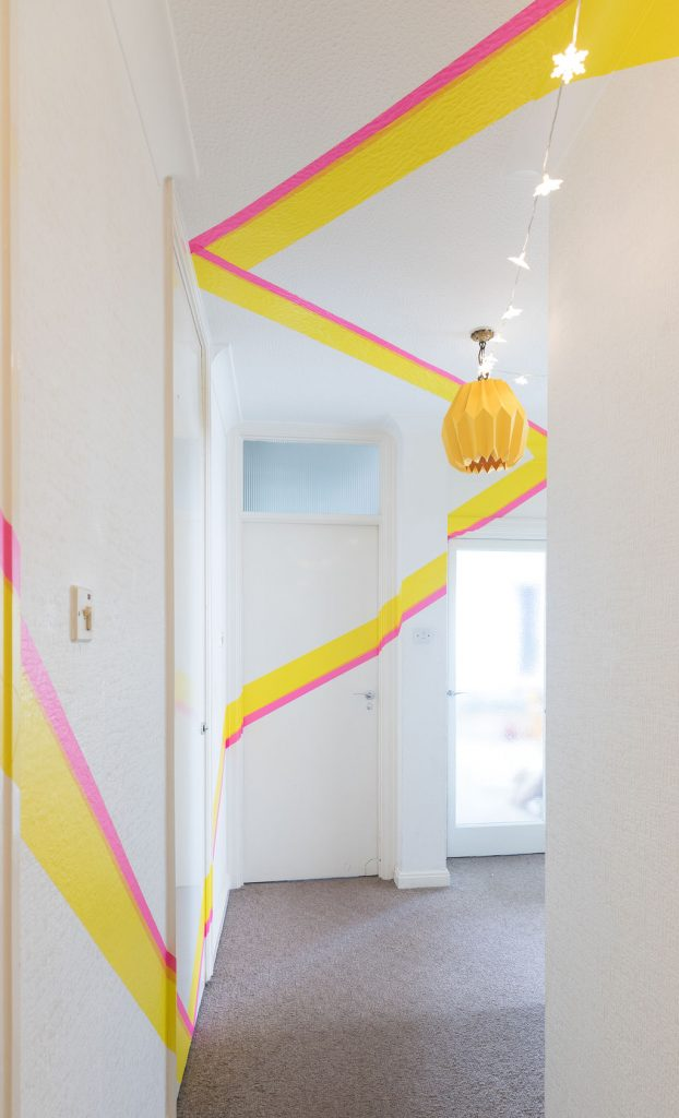 Stylish white corridor decorated with pink and yellow painting and fairy lights by Absolute Project Management