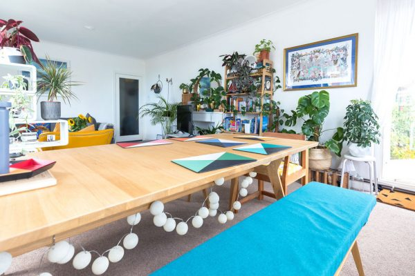 Turquoise dining space in a lovely and very fresh living room with many plants designed by Absolute Project Management