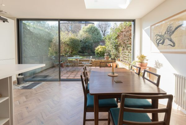 Dining room with beautiful view of garden through large patio doors - renovation by Absolute Project Management