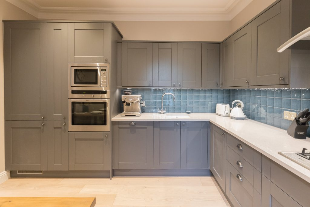 Grey kitchen with blue tiled splash back. Designed by Absolute Project Management