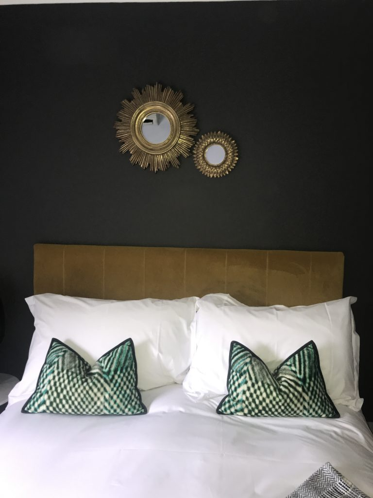Dark Grey bedroom with green cushions and mirror styled by APM