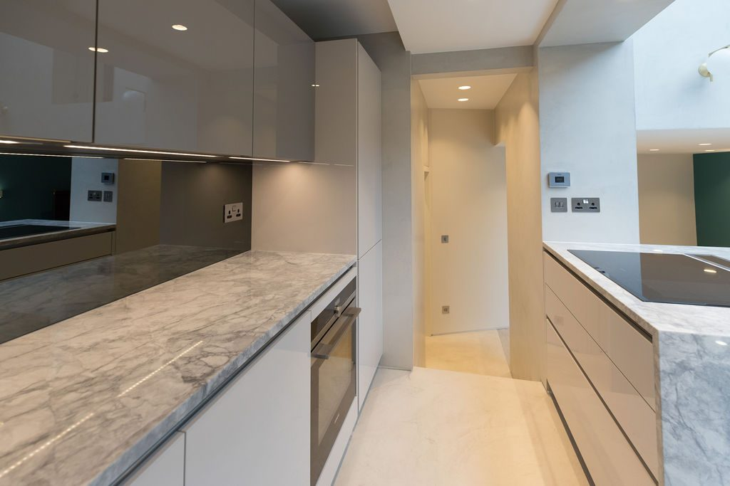 Sleek modern grey and marble kitchen in flat designed by Absolute Project Management