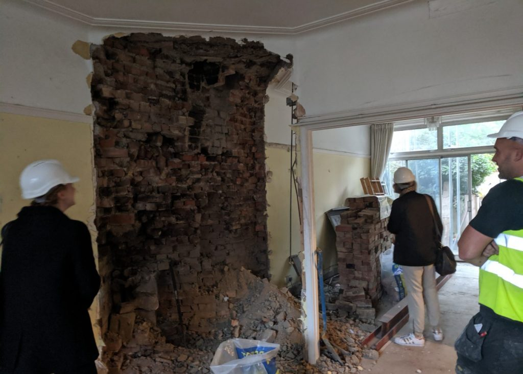 APM team inspect stripped out chimney breast with contractor on site