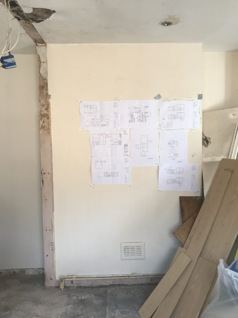 Renovation designs taped to wall on building site