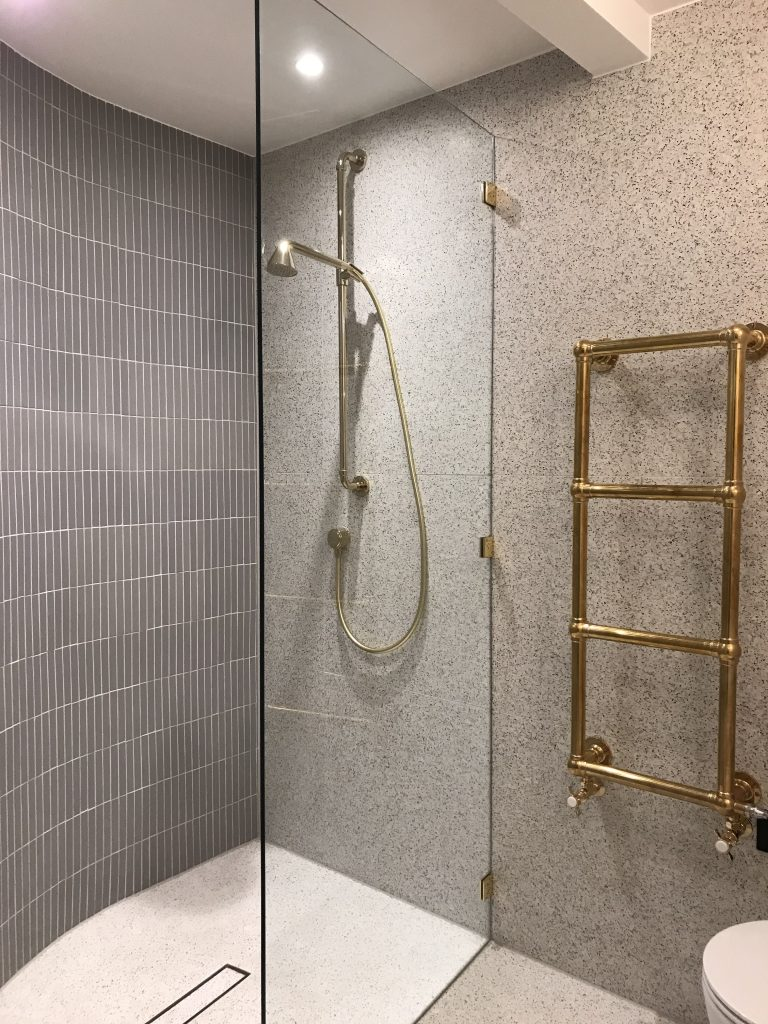 Shower with curved wall and slot drain - designed by Absolute Project Management