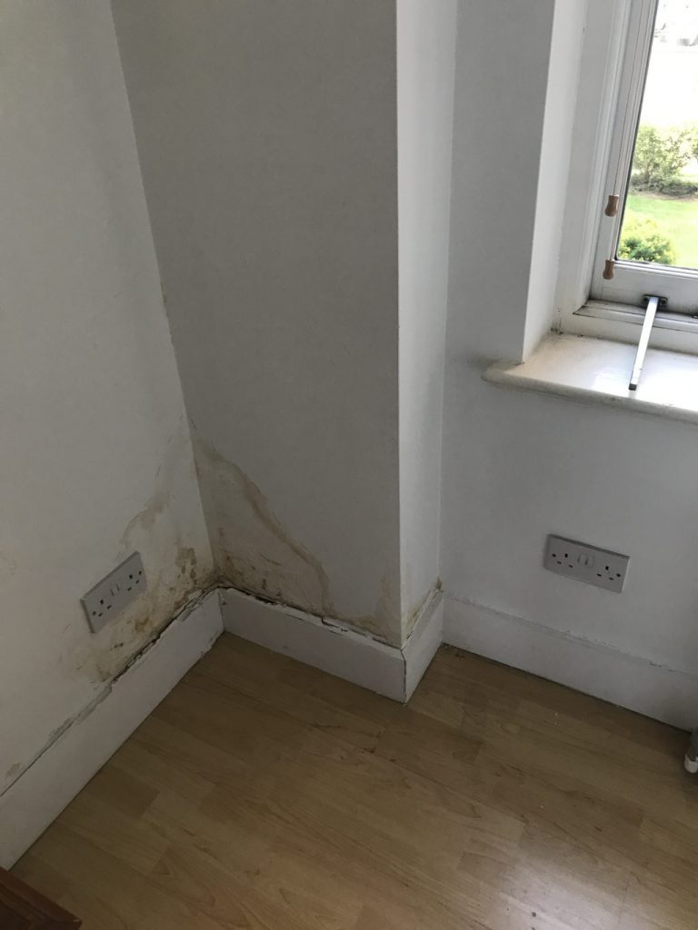 Stain caused by water penetration above skirting board in corner of room