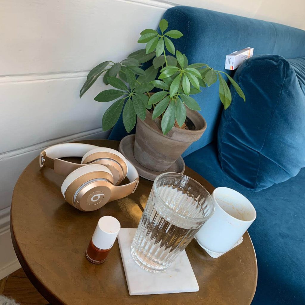 Attractive velvet sofa and round side table with beats headphones, water and umbrella plant