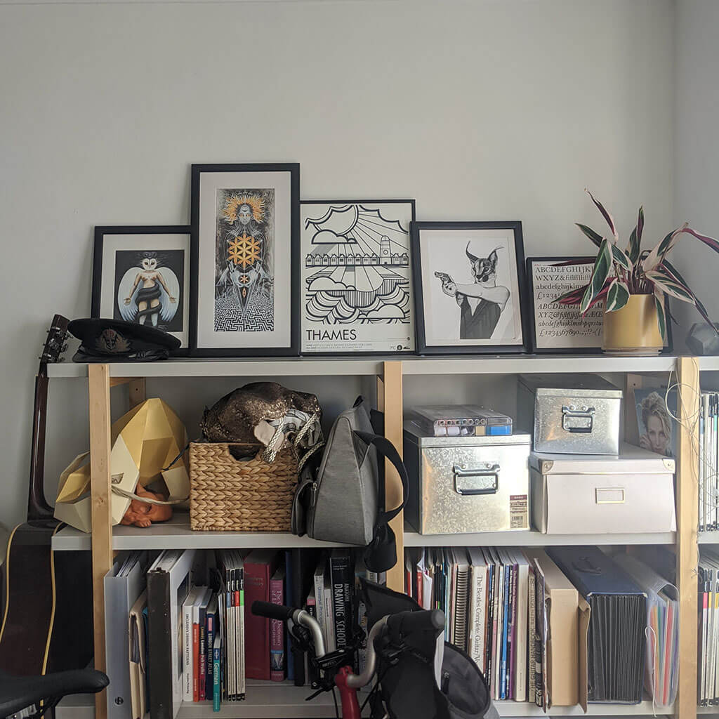 Artwork on top of a shelf of books and boxes in a home office