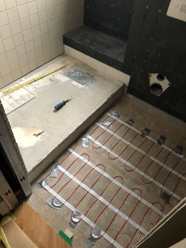 Bathroom floor with electric under-floor heating and step up into shower area