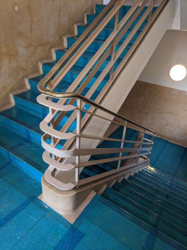 Staircase in Bauhaus building with blue plastic protective sheeting during renovation work