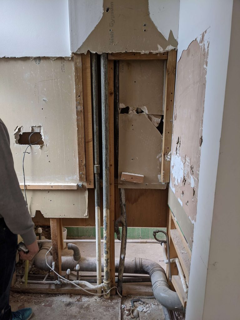 Old pipework exposed in a wall in flat during renovation