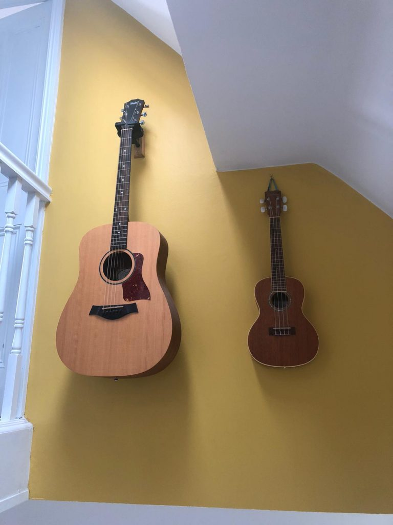 Guitars mounted on a wall painted in Farrow and Ball babouche in a house renovated by Absolute Project Management