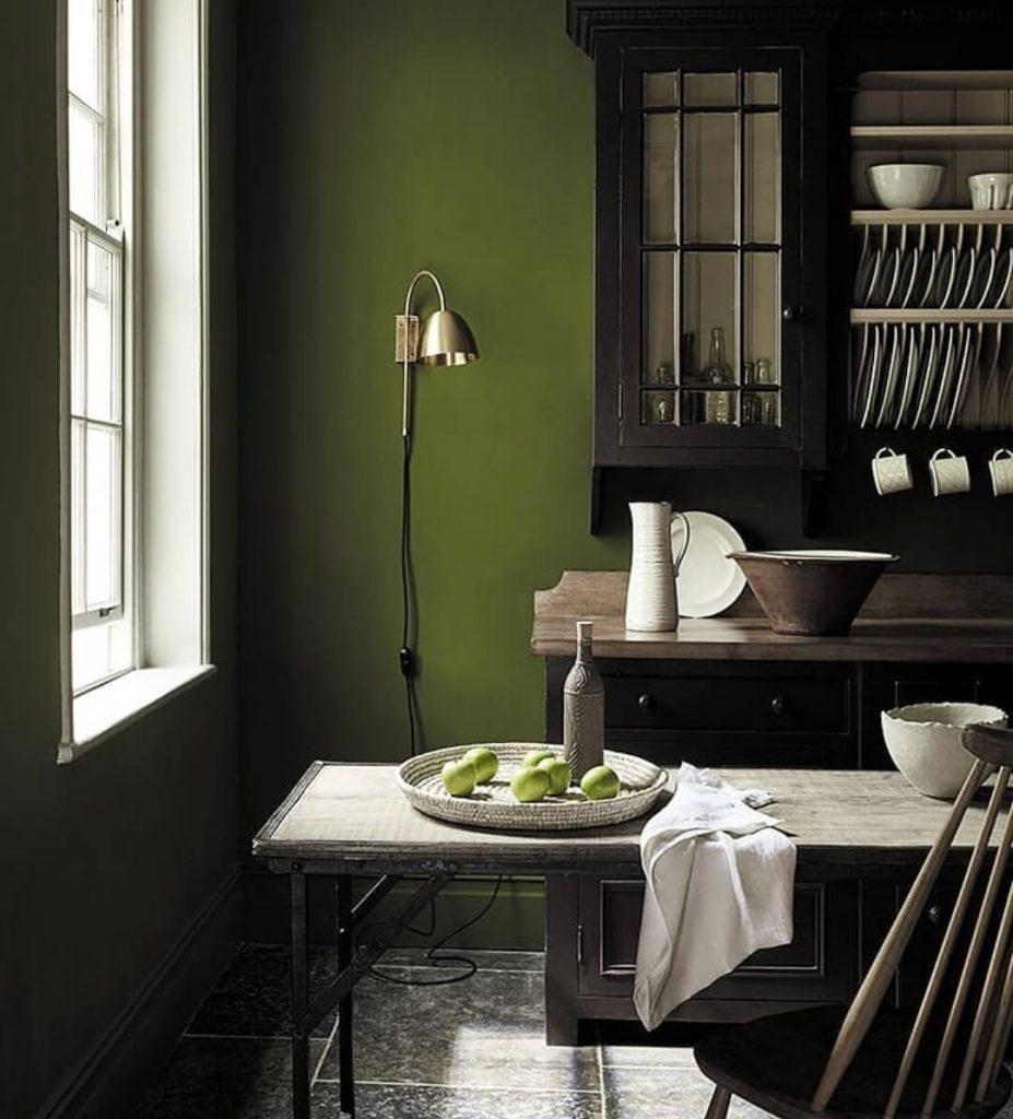 Brass wall light on green wall by Spark & Bell