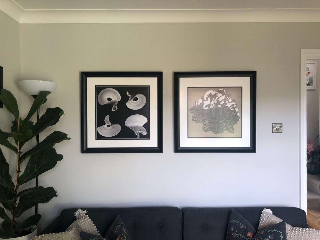 Two square artworks in black frames on a grey wall in a stylish living room design by Absolute Project Management