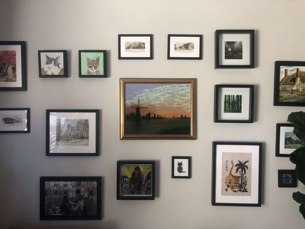 Gallery wall with gold and black frames on a grey painted wall in living room designed by Absolute Project Management.