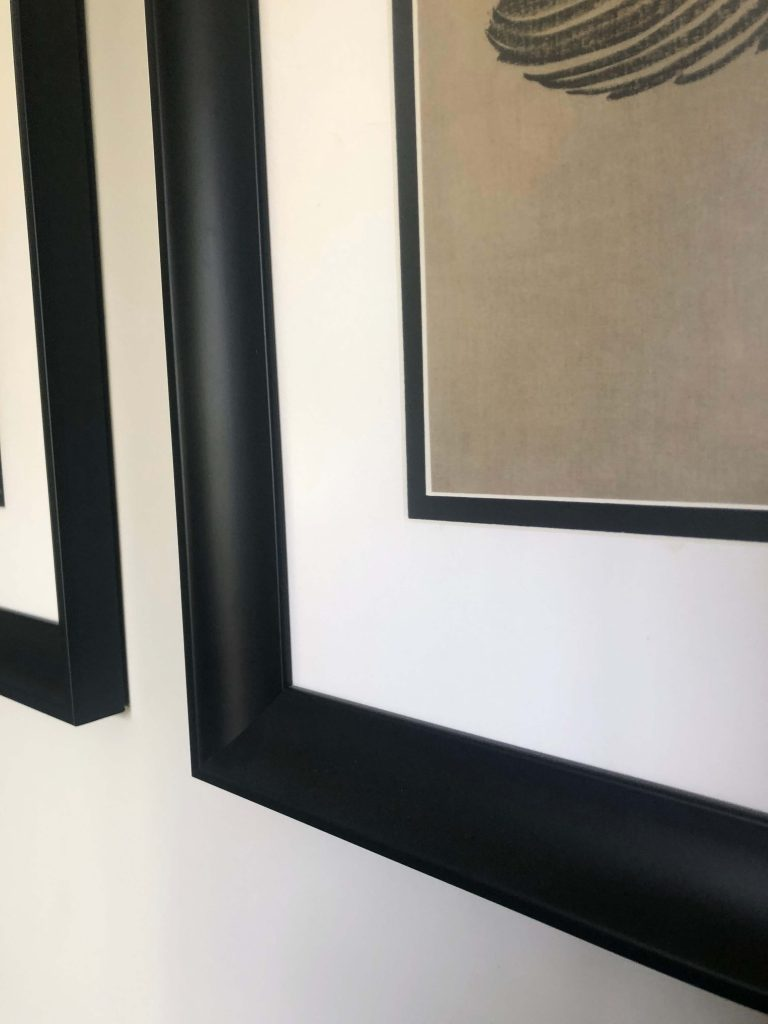 Close up of picture mount with small black border and white mount inside black frame