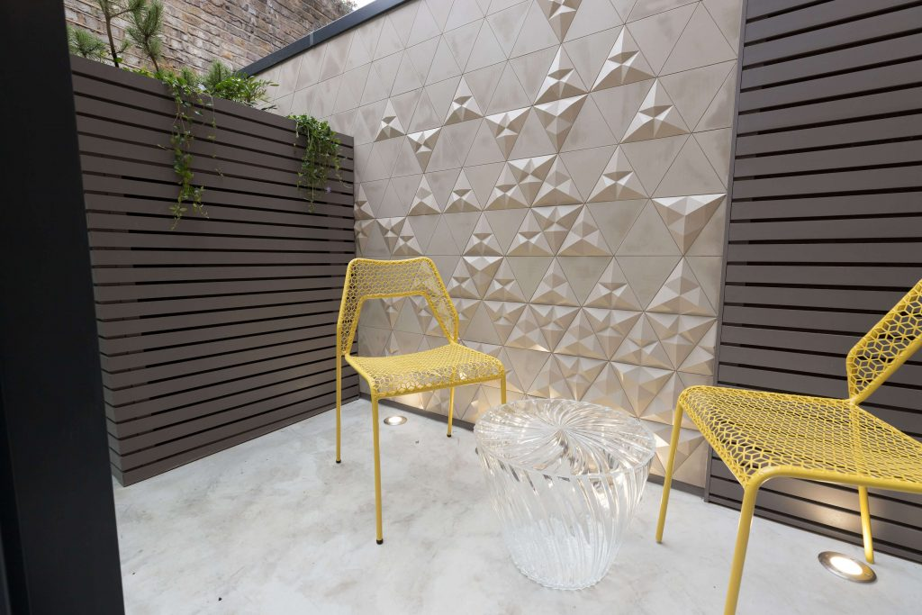 Geometric concrete tiles and garden joinery in dark grey-brown with yellow chairs