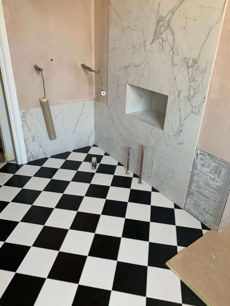 Bathroom renovation in progress with black and white floor tiles and marble effect wall tiles