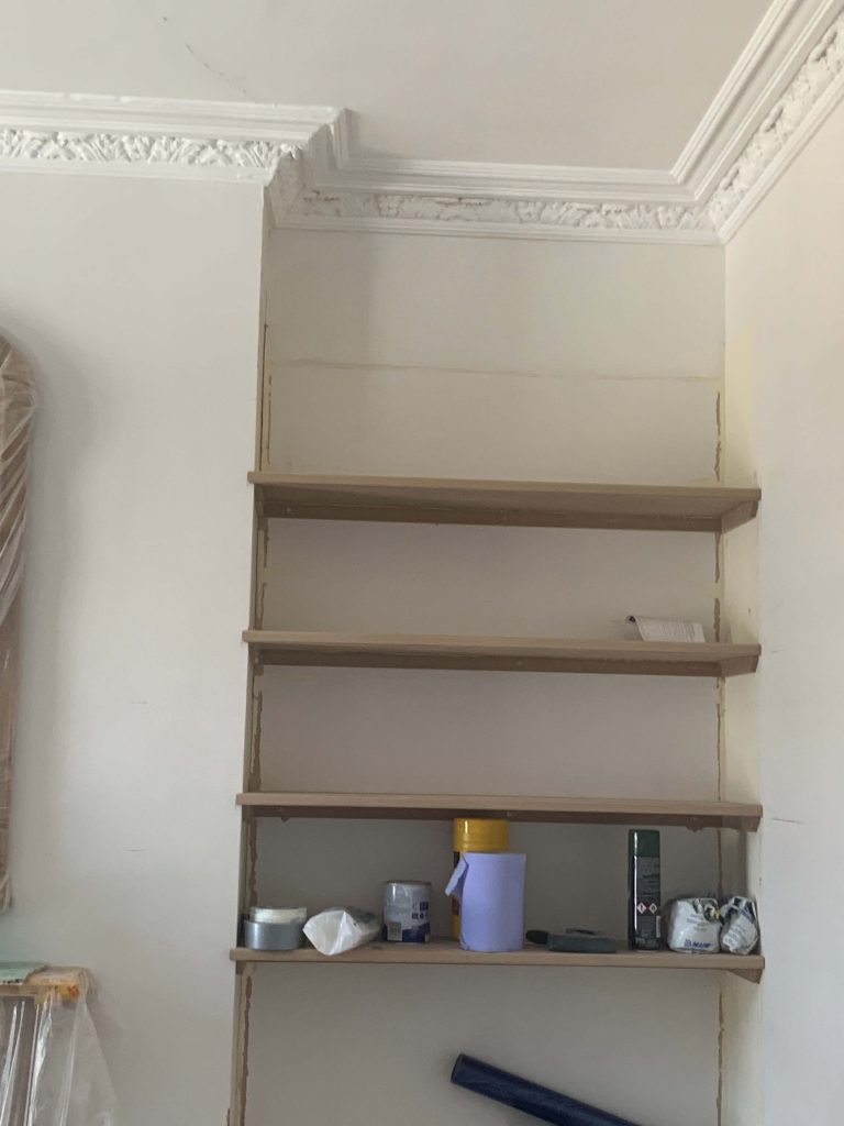 Shelves being built next to chimney breast with cornice details.