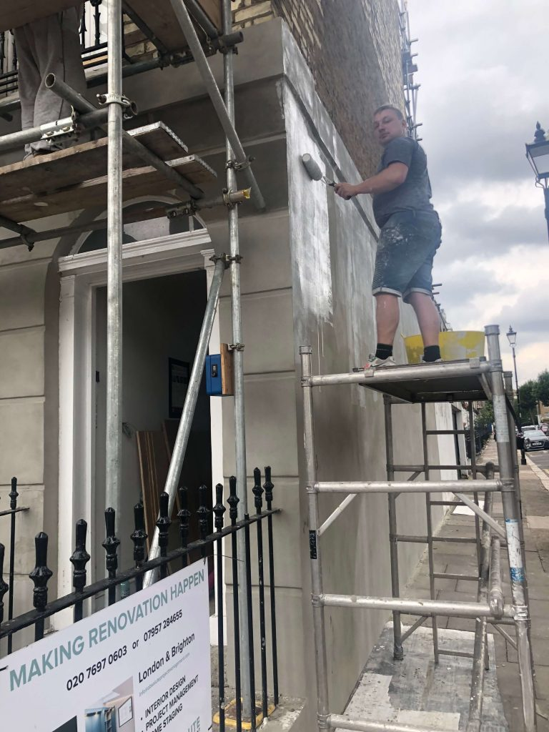 Decorator standing on scaffolding tower while painting the outside of a flat in London