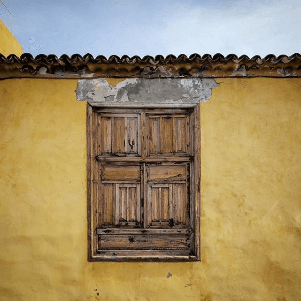 Yellow Ochre Wall with wooden shutters and peeling paint - seen on travels by Absolute Project Management
