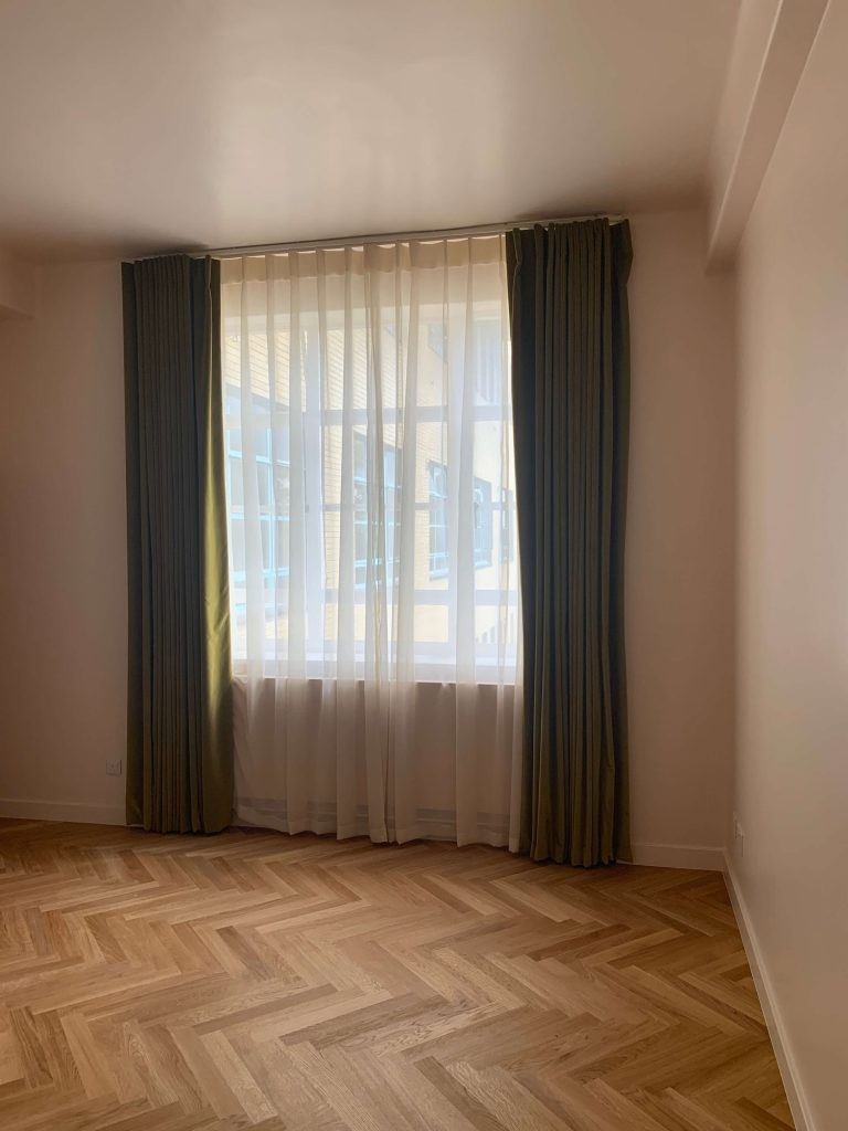 Olive green velvet curtains and cream sheer curtains cover a large window, next to a parquet wooden floor