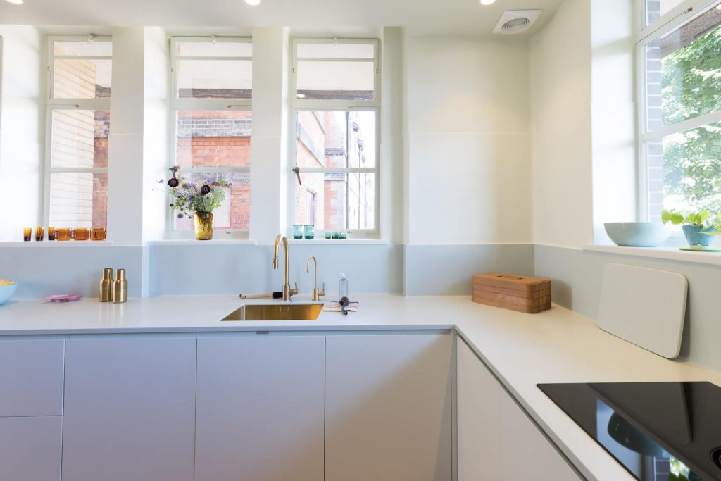 Soft green kitchen cabinetry, worktop, splash and walls. Renovation by Absolute Project Management.
