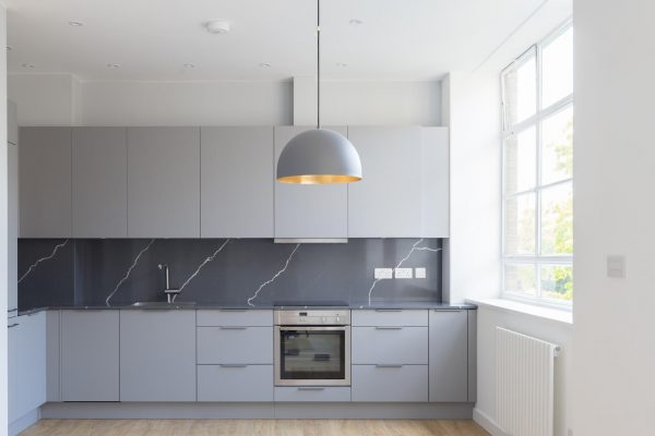 Grey kitchen with feature quartz splash back, as part of 2 adjoining flats remodel and renovation by Absolute Project Management