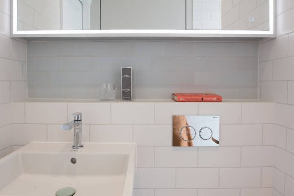 Compact bathroom with white tiles and built in mirror cabinet - renovation by Absolute Project Management