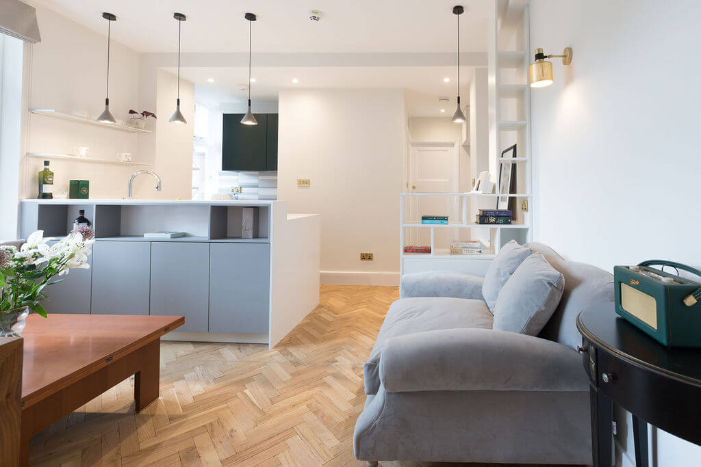 Living room and kitchen with wooden parquet floor, grey sofa and hanging concrete pendant lights - renovation by Absolute Project Management