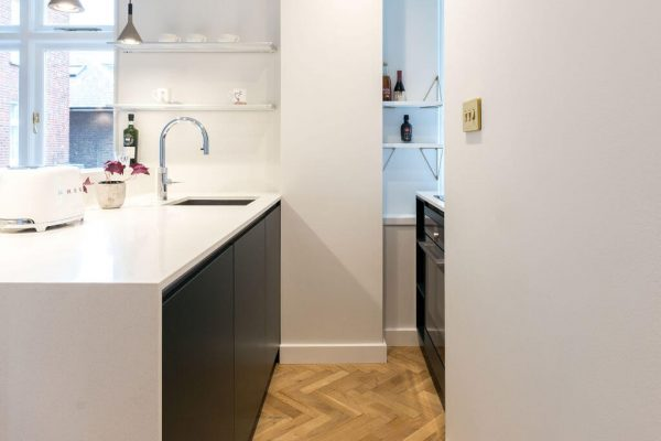 Kitchen with dark green and white cabinets, wooden parquet floor, and hanging concrete pendant lights - renovation by Absolute Project Management