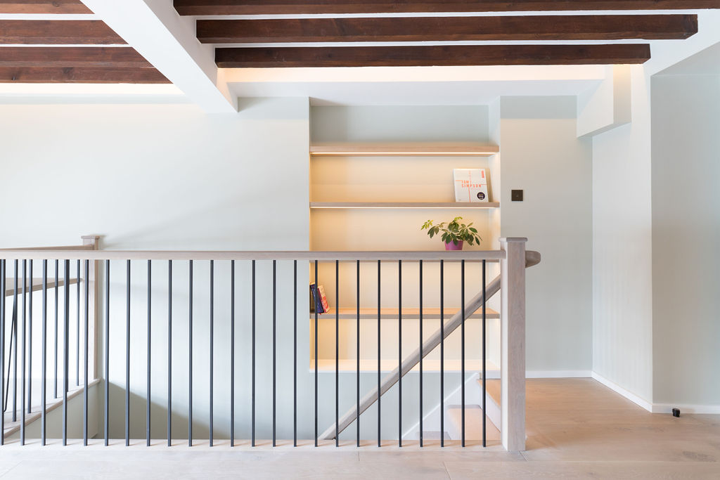 Industrial + oak bespoke balustrade, alcove shelving, timber joists, oak flooring and soft green walls - renovation by Absolute Project Management