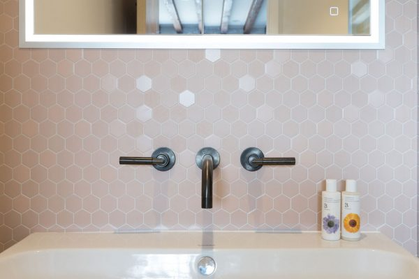 Blush hexagon wall tiles, with sleek industrial platinum matt tapware and crisp white sanitaryware - renovation by Absolute Project Management