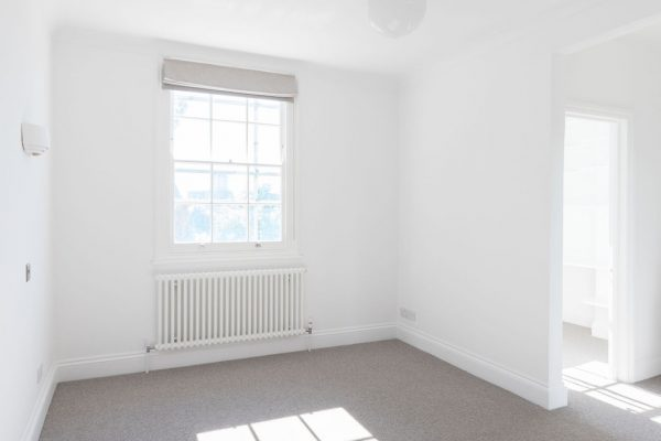 Newly redecorated room with large windows, white walls and grey carpet - renovation by Absolute Project Management