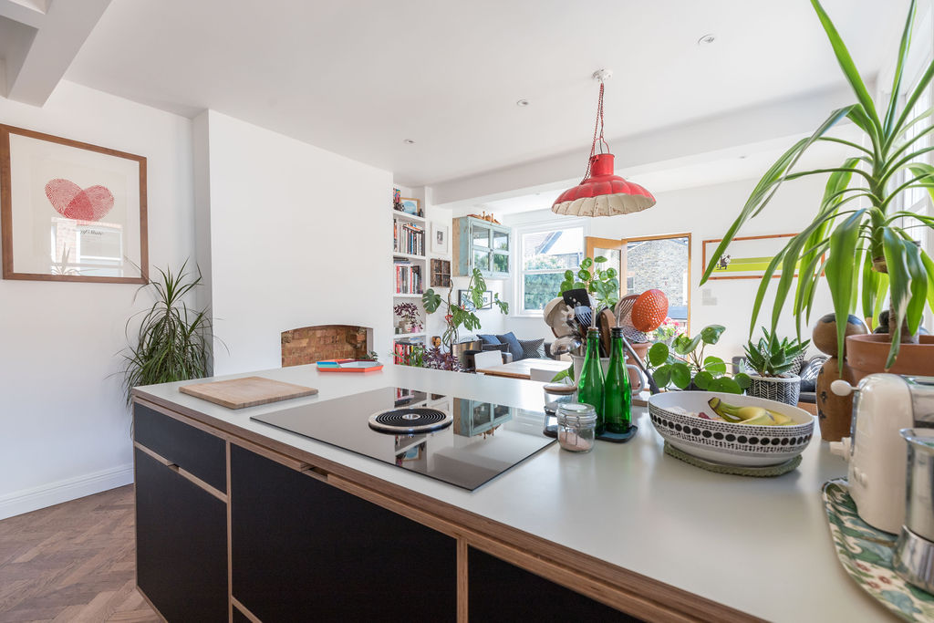 Carefully selected vintage items and indoor plants work beautifully with this black plywood kitchen. Renovation by Absolute Project Management.