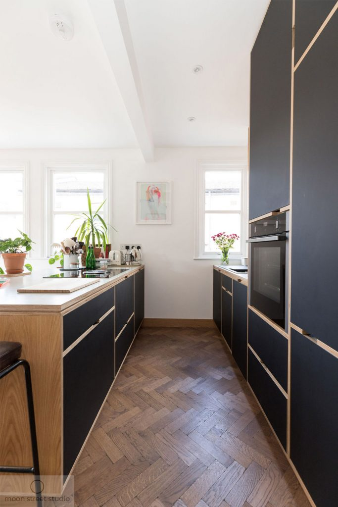 Modern black ply kitchen cabinetry with parquet wood flooring creates a stunning kitchen. Renovation by Absolute Project Management.