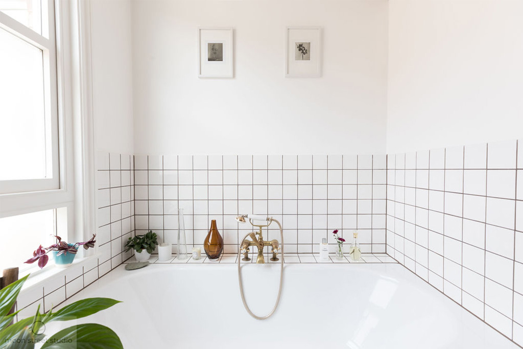 Beautiful brass tapware and carefully selected decorative items add a luxurious touch to this fresh white bathroom. Renovation by Absolute Project Management.