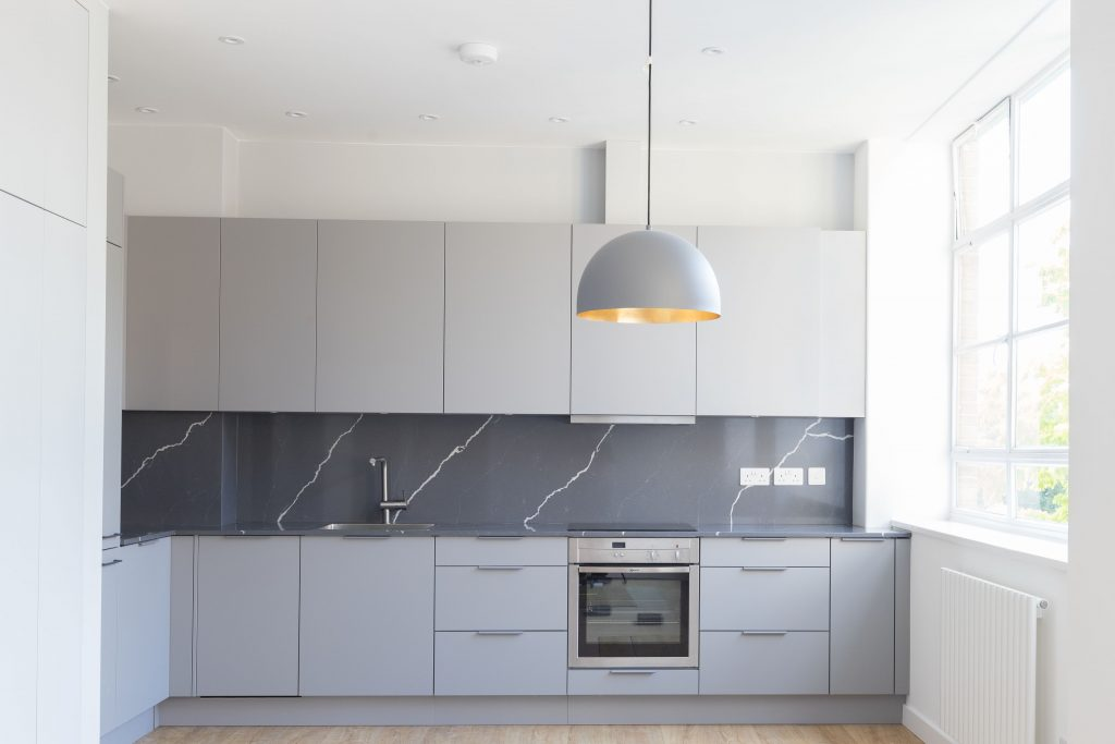 Soft grey kitchen cabinetry with a darker worktop and modern fittings keep this space contemporary. Renovation by Absolute Project Management.